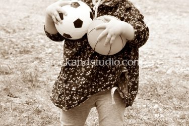 Girl In Knitted Hat With Balls – Sepia